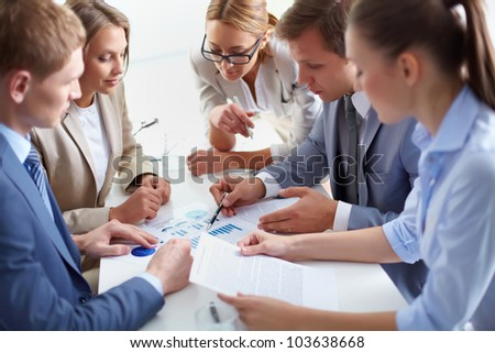 Image of business partners discussing documents at meeting - stock photo