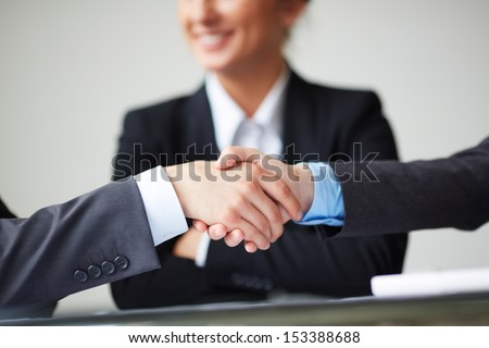 Image of business partners handshaking on background of businesswoman - stock photo