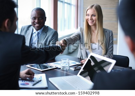 Image of business partners handshaking on background of their colleague - stock photo