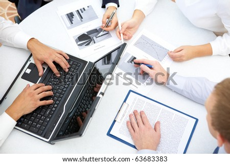 Image of business people hands working with papers and typing at meeting