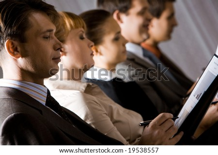 Image of business people holding  papers and making notes on them