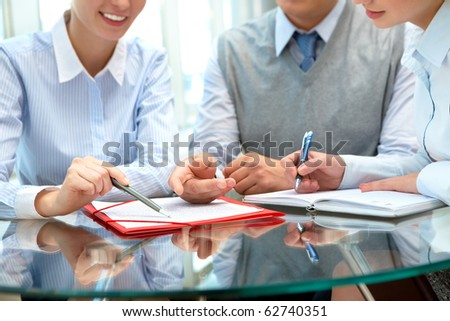 Image of business people sharing ideas round the table at meeting - stock photo