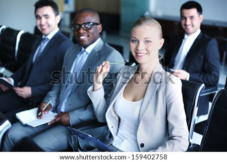 Image of business people sitting in rows at seminar - stock photo