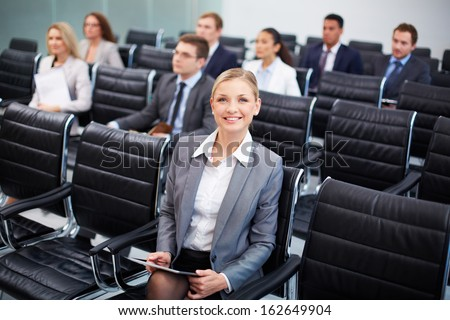 Image of business people sitting in rows at seminar with pretty woman in front - stock photo