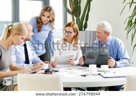Image of business people working at office. Busy businesswomen and businessmen sitting at conference desk in front of laptop and working on financial plan.