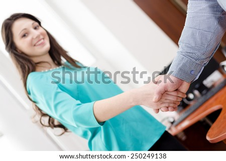 Image of business woman and man shaking hands closeup in office - stock photo