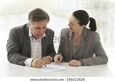 Image of business woman pointing document to business man  for signature  at the office