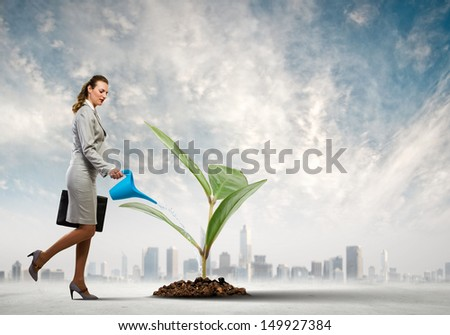 Image of business woman watering sprout. Ecology concept