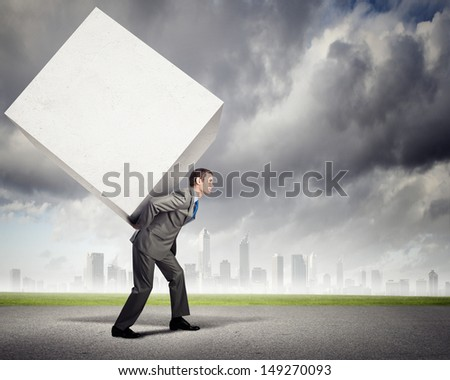Image of businessman carrying big white cube on his back