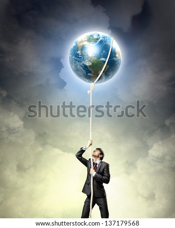 Image of businessman climbing rope attached to earth planet. Elements of this image are furnished by NASA - stock photo