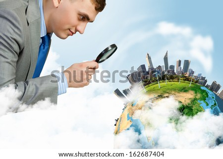 Image of businessman examining objects with magnifier. Elements of this image are furnished by NASA - stock photo
