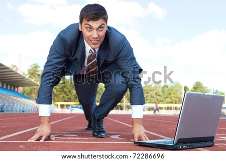 Image of businessman getting ready for race with laptop near by - stock photo