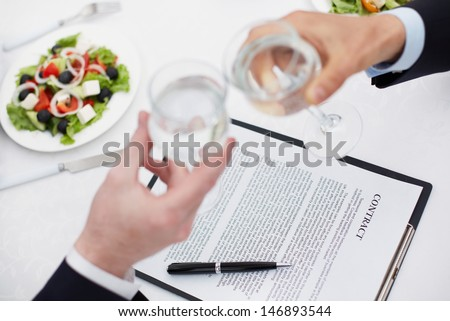 Image of businessman hands toasting with glasses with signed contract near by - stock photo