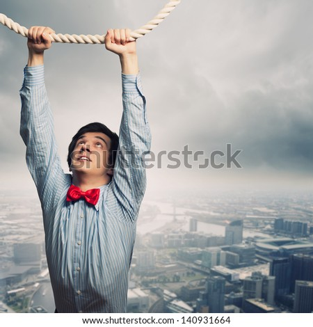 Image of businessman hanging on rope against city background - stock photo