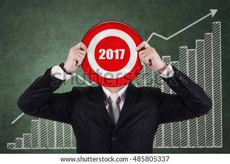 Image of businessman holding a dartboard with numbers 2017 in front of financial chart