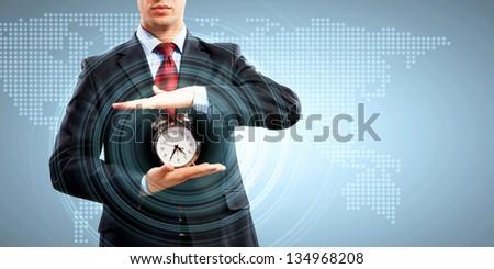 Image of businessman holding alarmclock against illustration background - stock photo