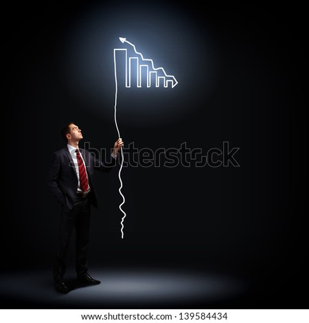 Image of businessman in black suit against dark background - stock photo