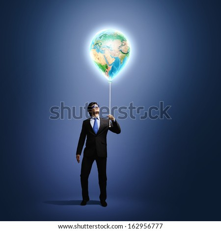 Image of businessman in goggles holding globe. Protect planet.