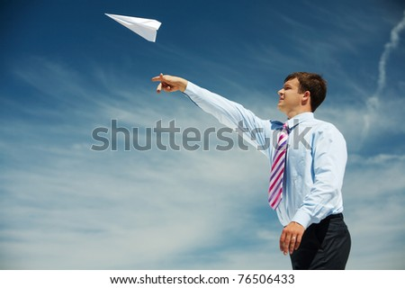 Image of businessman letting paper airplane fly and looking at it on background of blue sky