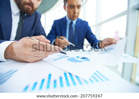 Image of businessman pointing at paper during discussion with his partner at meeting