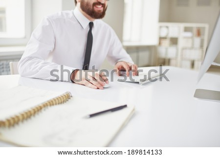 Image of businessman sitting in office and computing