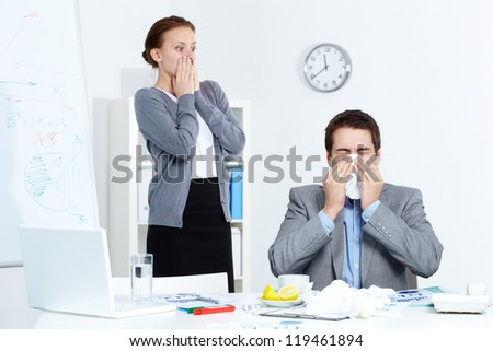 Image of businessman sneezing while his partner looking at him with fright in office - stock photo