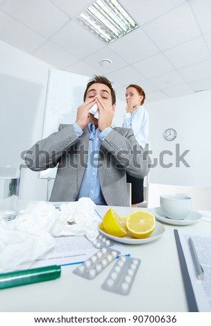 Image of businessman sneezing while his partner on background looking at him with fright in office - stock photo