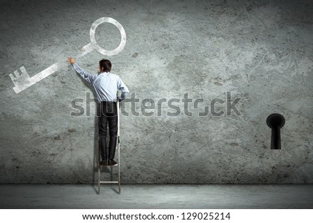 Image of businessman standing on ladder holding key - stock photo