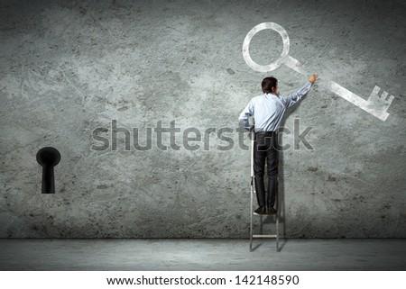 Image of businessman standing on ladder holding key - stock photo