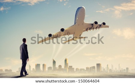 Image of businessman standing with back looking at airplane in sky