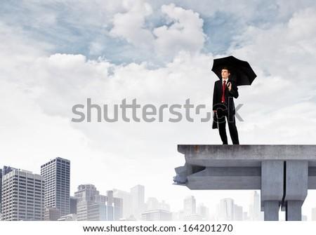 Image of businessman with umbrella standing at the edge of bridge - stock photo