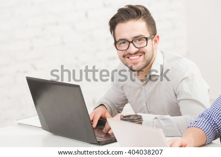 Image of businessman working in office in front of his laptop computer. Happy man in glasses toothy smiling.