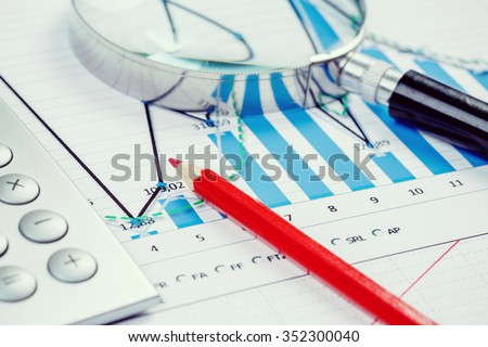 Image of businessman workplace with papers and magnifying glass