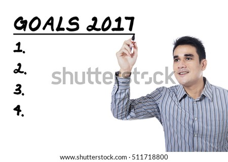 Image of businessman writing his goals in 2017 with a marker on the whiteboard