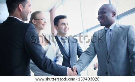 Image of businessmen handshaking on background of their colleagues - stock photo