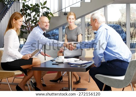 Image of businessmen shaking hands while business people sitting around the tablet and making deal. Teamwork at office.  - stock photo