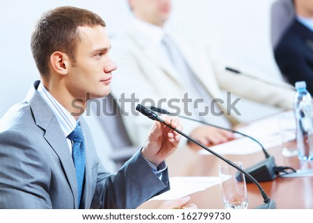 Image of businessmen speaking in microphone at conference - stock photo