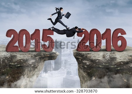 Image of businesspeople work together to pass the cliff with numbers 2015 and 2016 - stock photo