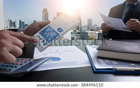 Image of businessperson pointing at document in touchpad at meeting,filter sun - stock photo
