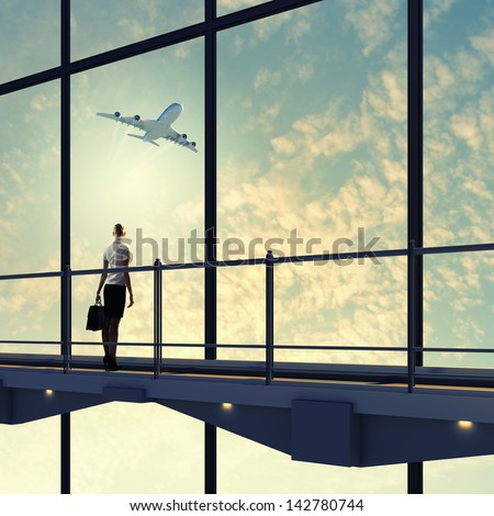 Image of businesswoman at airport looking at airplane taking off - stock photo