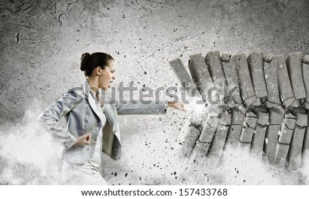 Image of businesswoman breaking bricks with hand