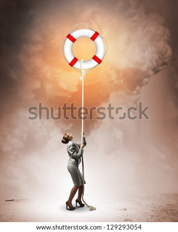 Image of businesswoman climbing the rope attached to lifebuoy - stock photo