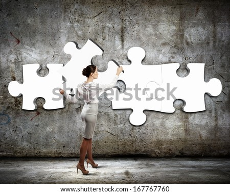 Image of businesswoman connecting elements of white puzzle - stock photo