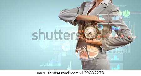 Image of businesswoman holding alarmclock against illustration background - stock photo