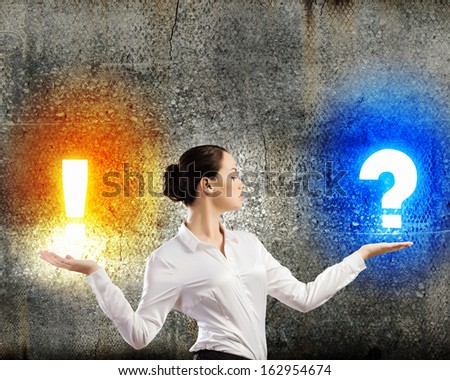 Image of businesswoman holding exclamation and question marks on palms - stock photo