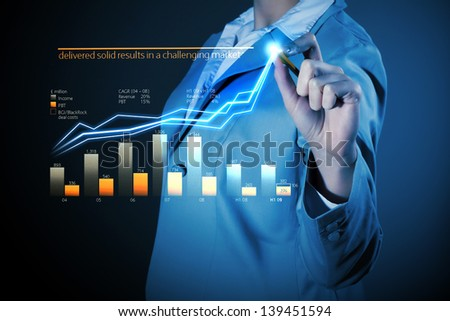 Image of businesswoman in grey suit drawing graph - stock photo