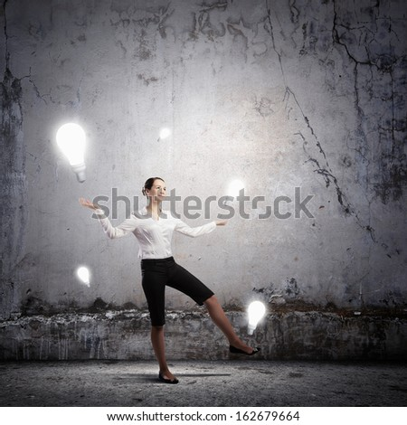 Image of businesswoman juggling with electrical bulbs - stock photo