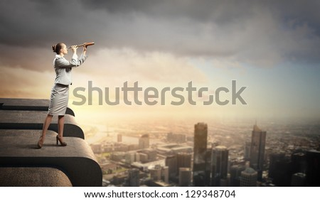 Image of businesswoman looking in telescope standing a top of building - stock photo