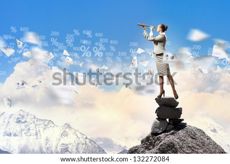Image of businesswoman looking in telescope standing a top of rock - stock photo