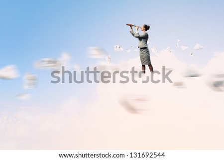 Image of businesswoman looking in telescope standing against clouds background - stock photo